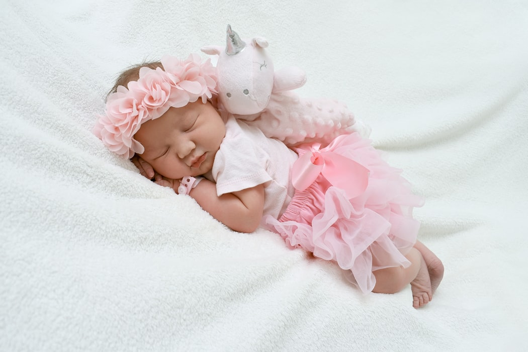 sleeping infant with pink tutu and pink flower headband on white blanket